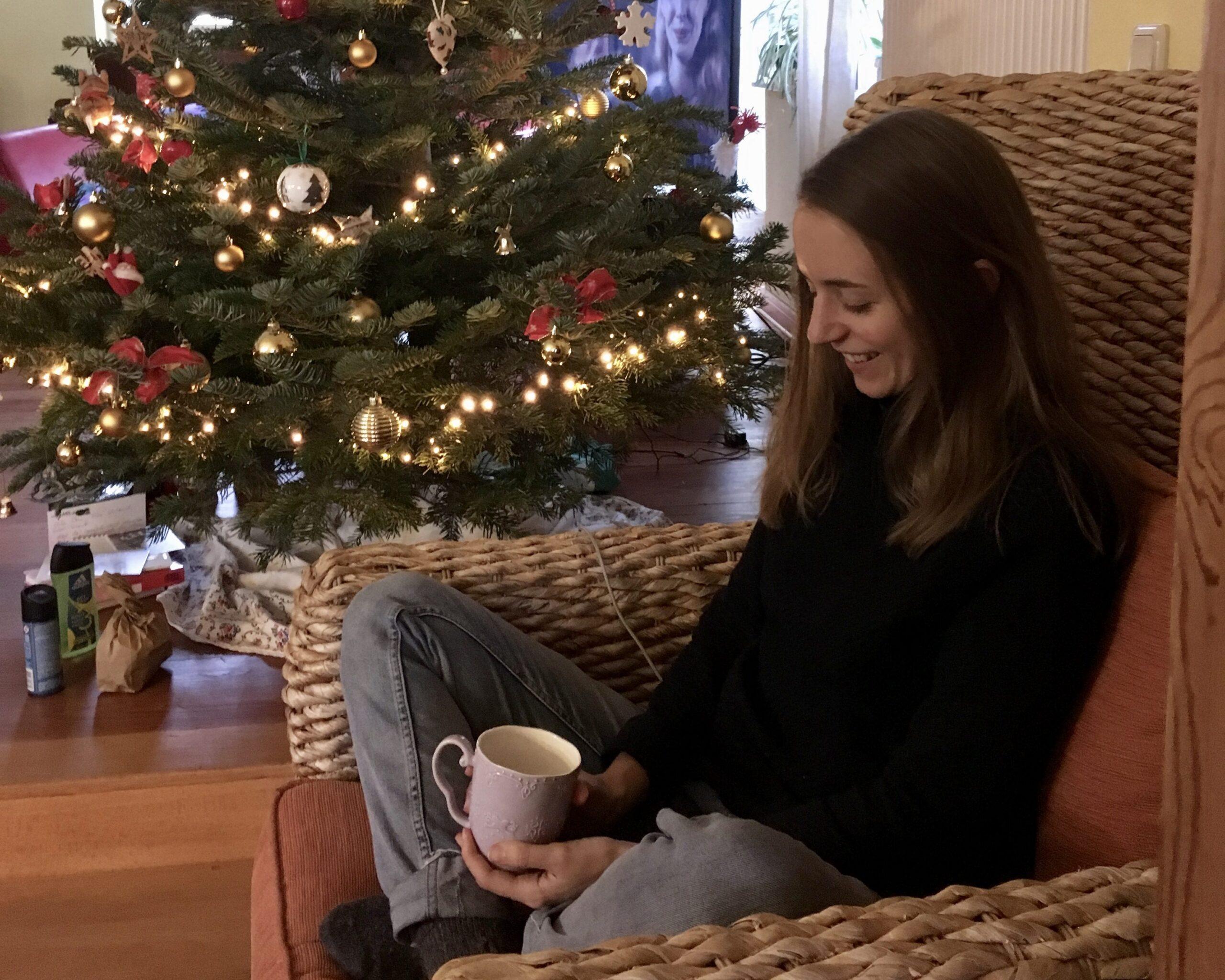 Miriam Hanika sitzt mit einer Tasse auf einem Korbsessel neben dem Weihnachtsbaum.
