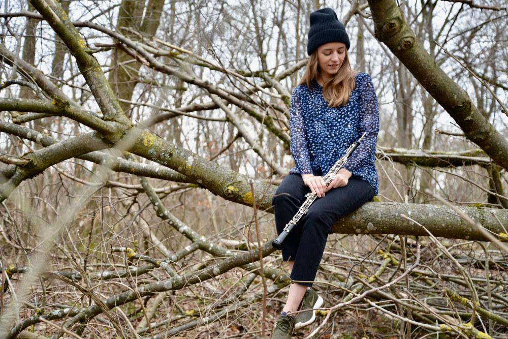 Miriam Hanika sitzt mit ihrer Oboe auf einem Baum im Wald.