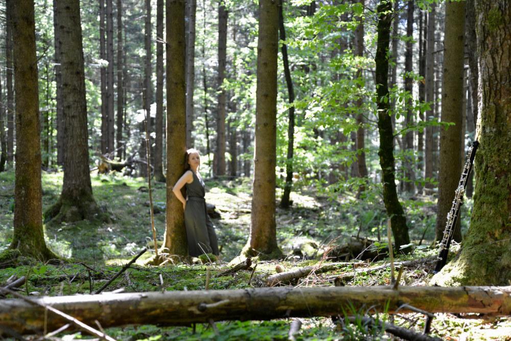 Miriam Hanika lehnt an einem Baum im Wald und wartet