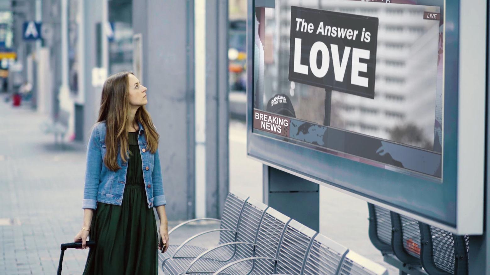 Miriam Hanika auf Reisen, vor ihr ein Schild: The answer ist love.