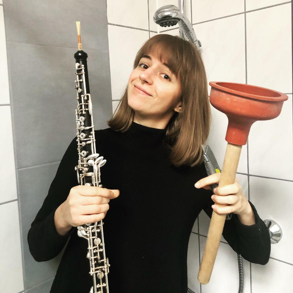 Miriam Hanika mit ihrer Oboe und einem Klo-Pömpel.