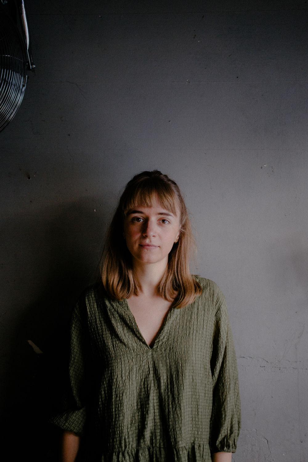 Miriam Hanika, Portrait vor grauer Wand.