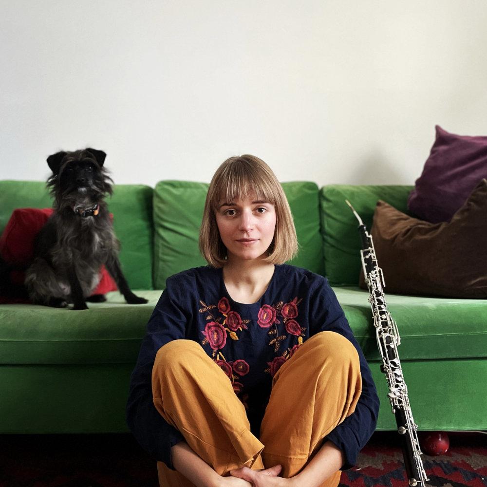 Miriam Hanika mit ihrem Englisch Horn und ihrem Hund Mina vor einer grünen Couch