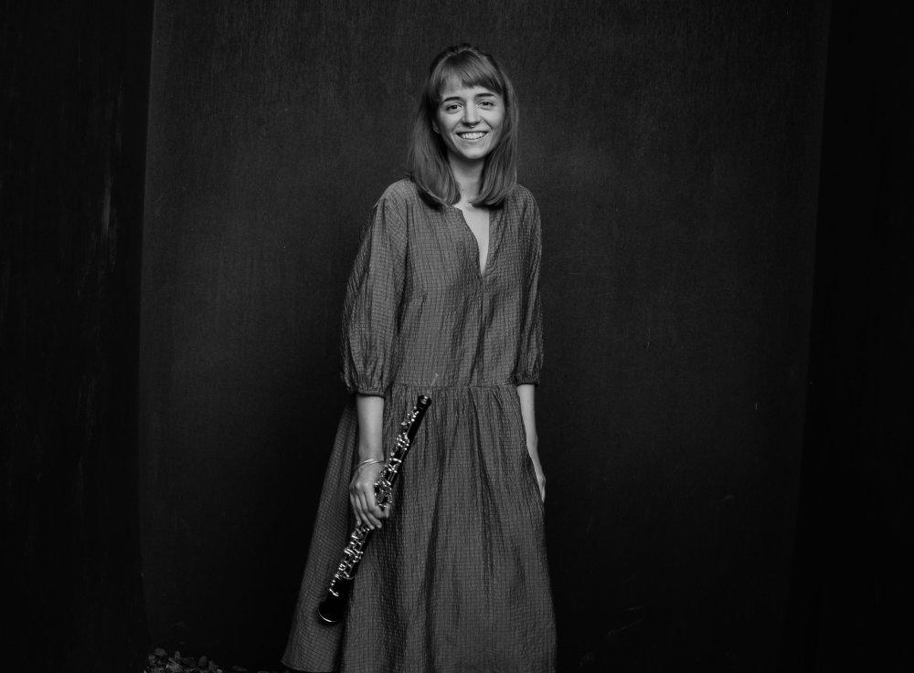 Miriam steht lachend mit Oboe vor schwarzer Wand