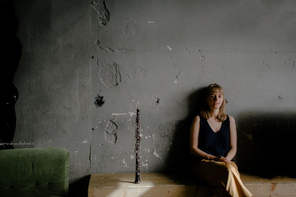 Miriam Hanika mit ihrer Oboe vor einer grauen Wand